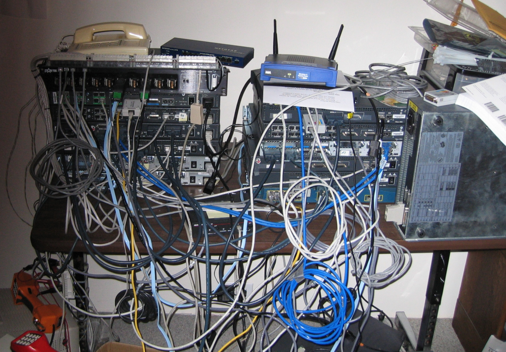 The author's 2004 lab. Not neat! Note the but sets for VoIP testing, the 3000-series lying vertically on the right, and the small black ISDN sim on the table, center-front.
